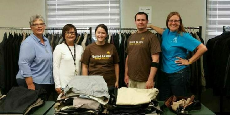 UPS volunteers and Avivo staff pose in front of one section of suits at Men's Wearhouse Suit Giveaway