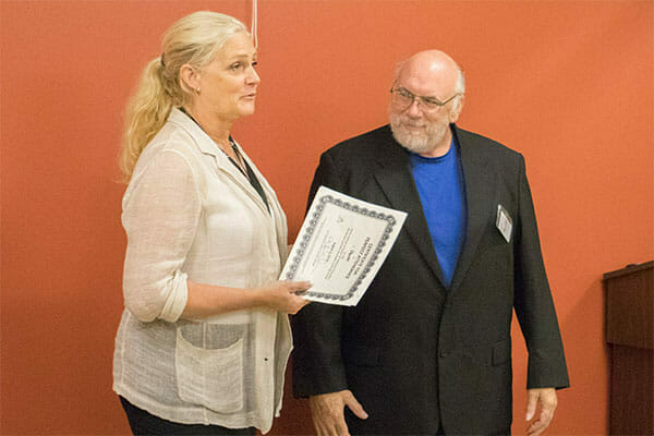 Jackie Travis, Avivo's Mobility Mentor, hands Dan his certificate of perfect attendance at his graduation ceremony.