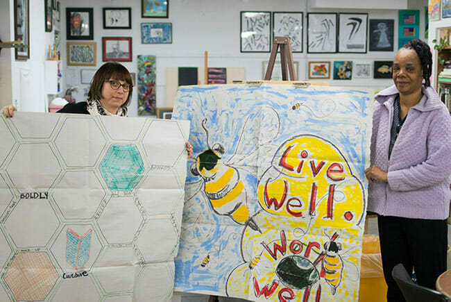 Two artists display a mural in the works as part of Avivo ArtWorks.