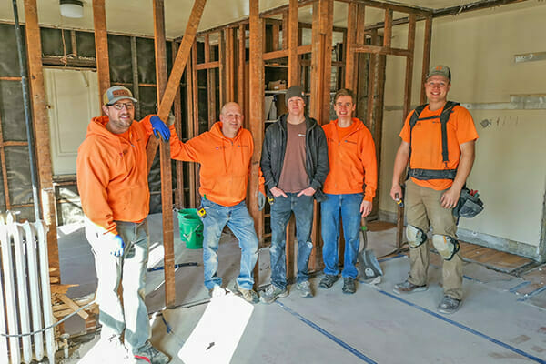 The team from build partner The Kingdom Builders, in the early stages of remodeling one of Avivo's family recovery housing units.