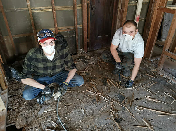 Two contractors from Plekkenpol Builders, Inc. assess the floor of one of Avivo's family recovery housing units in the early stages of renovations.